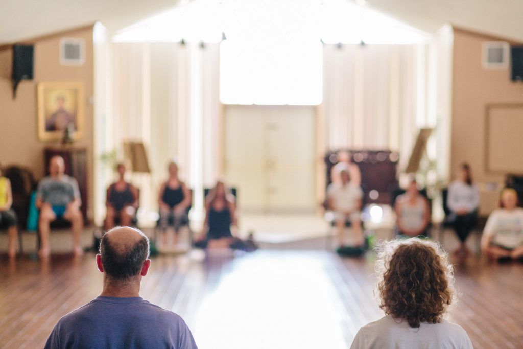 Large group meditating in a circle during a Mindful-Way meditation retreat